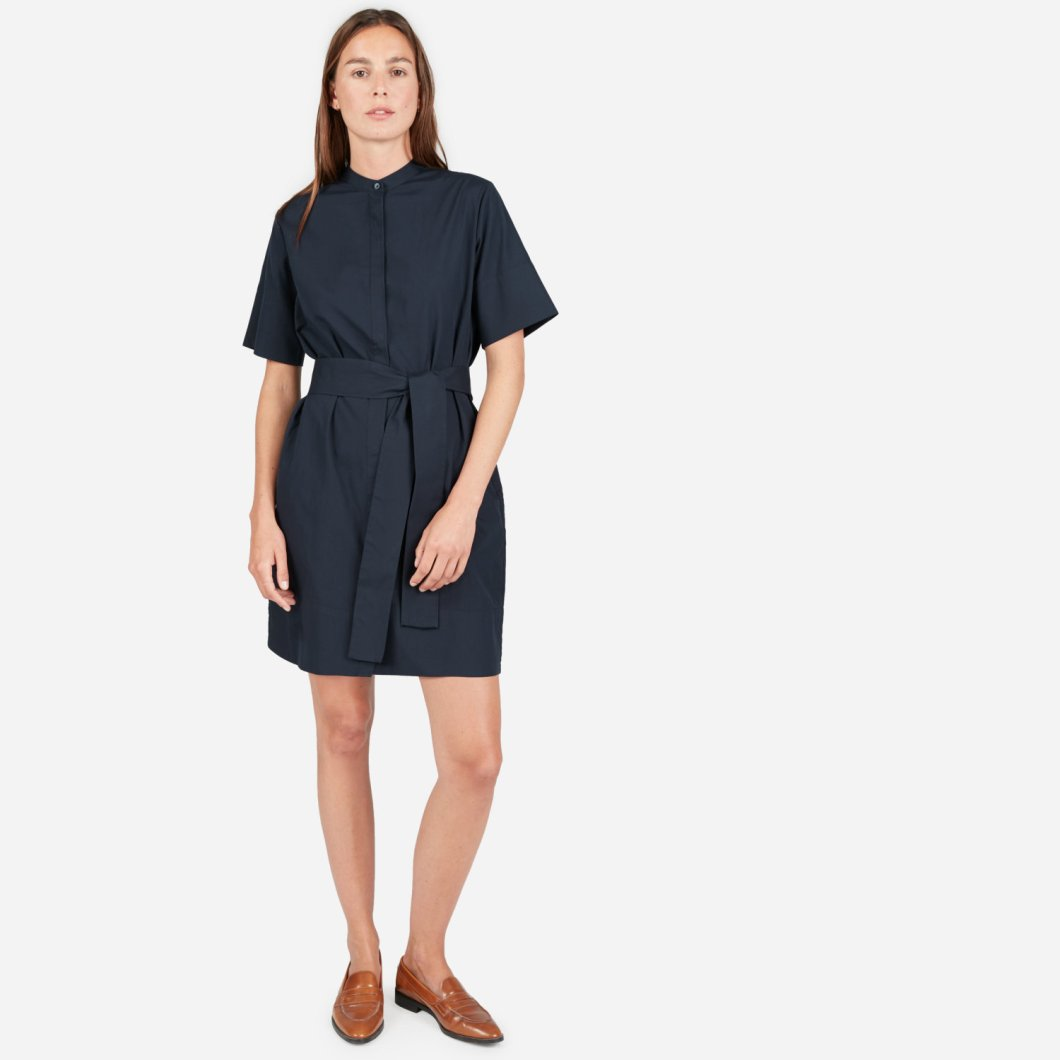 Dark navy collarless, above-the-knee-length dress with wide fabric belt tied at the waist in matching fabric.