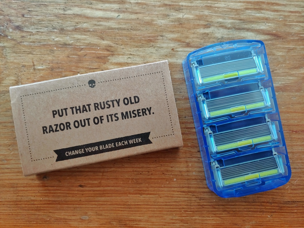 Dollar Shave Club razor set, with the phrase 'Put that rusty old razor out of its misery' and 'Change your blade each week' emblazoned beneath a small skull logo.