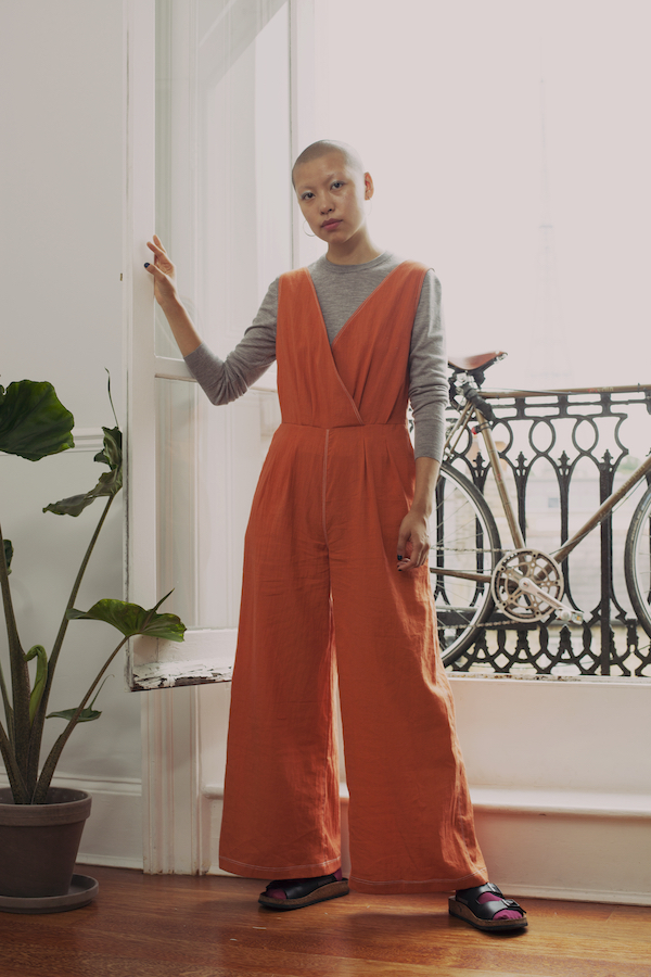 Sleeveless wrap-style jumpsuit with wide legs in burnt orange, worn over a grey long-sleeve t-shirt.