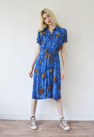 Knee-length blue and yellow floral dress, tied at the waste with a matching belt.