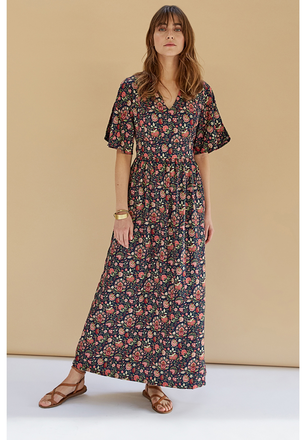 Floral print maxi dress of pink and green flowers on a base of dark blue.