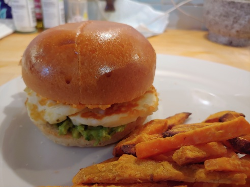 Halloumi, guacamole and houmous in a brioche burger on a white plate, next to a pile of sweet potato fries.