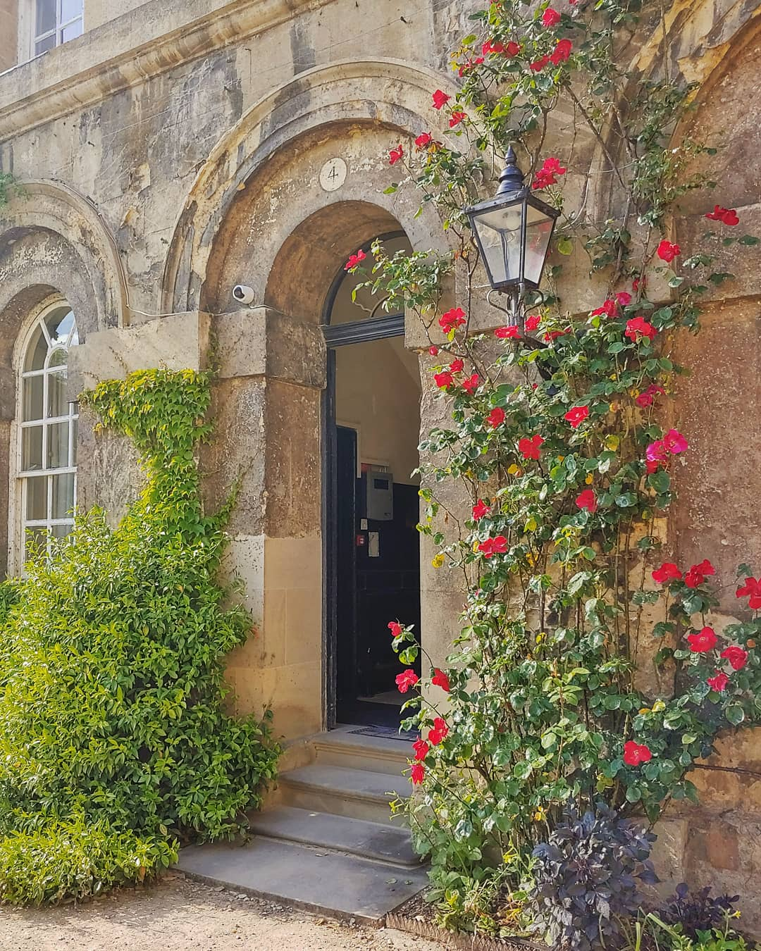 Stone doorway surrounded by red roses, at Worcester College Oxford.