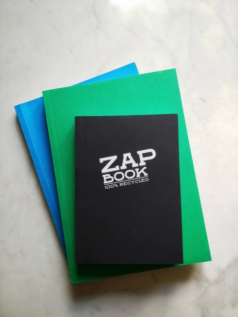 A pile of three Zap Notebooks, one blue and green in an A5 size, one smaller in black.  The black one reveals the cover, 'Zap Book 100% recycled in a bold modern font