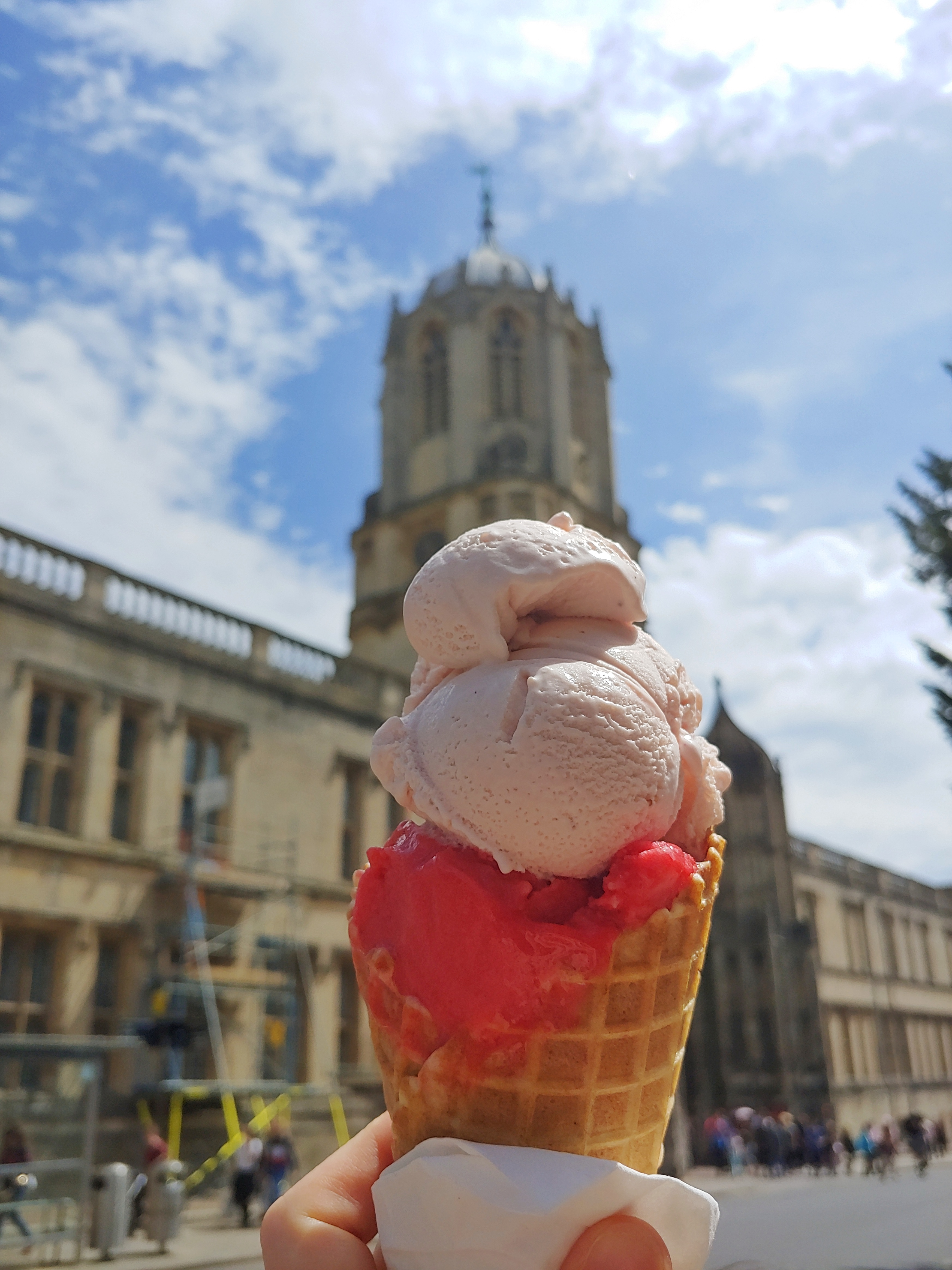 View of a cone of ice cream with light pink strawberry ice cream and deep pink raspberry sorbet, held in front of Christ Church's Tom Tower