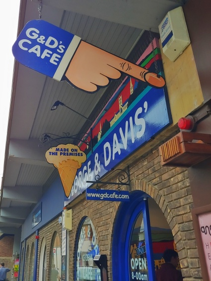 Image of the quirky signs over the store front, a big hand pointing to the door with G&D's Cafe, the other in the shape of an ice cream with 'Made on the Premises' written on it