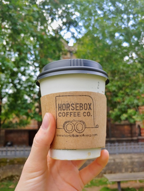 Image of coffee cup held up with trees and buildings of Keble College in the background.