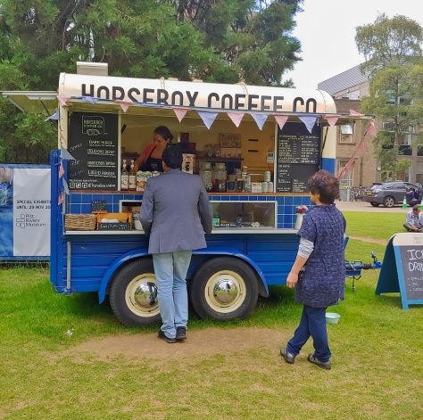 Image of a horsebox converted into a coffee bar, with someone making a coffee inside.