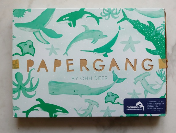 Box decorated with light-turquoise images of whales, with 'Papergang' cut-out.