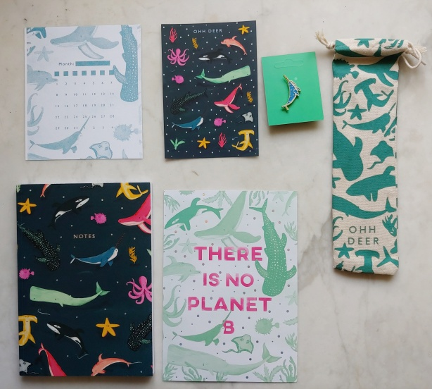 Small single-month calendar sheet, page of stickers, notebook, poster reading 'there is no Planet B', narwhal pin, and bag containing metal straws, all in various whale-based patterns