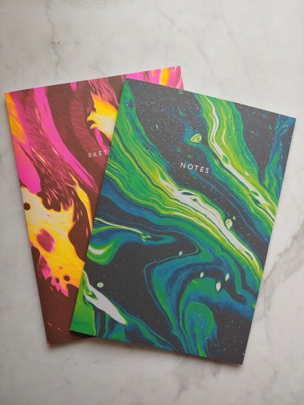 Two note-books with bright oil-spill patterns in green and pink.