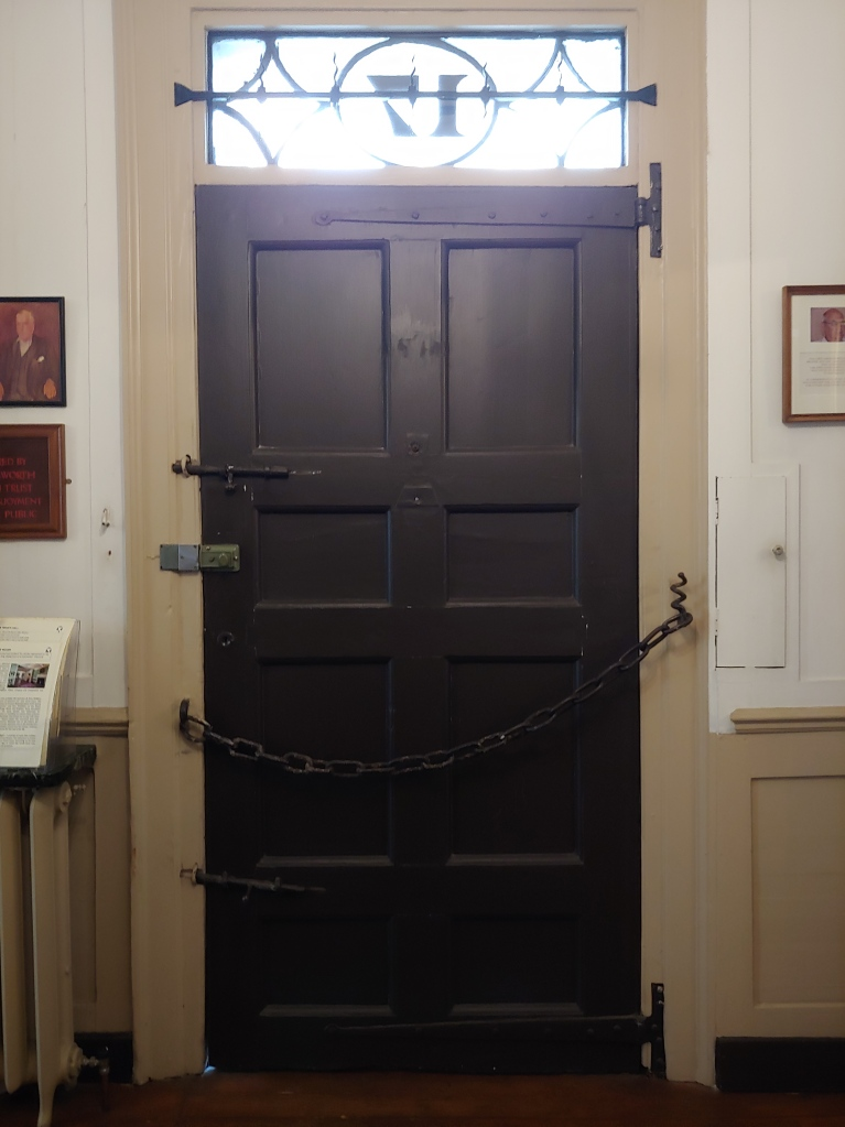 Internal shot of the front door, including the large chain and the protective spikes above.