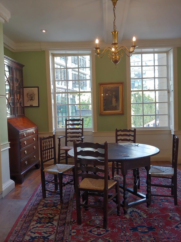 The dining room, with a wooden bureau bookcase in the corner, a painting on the wall, two sash windows looking out across to modern business buildings, and a small round table with four chairs.