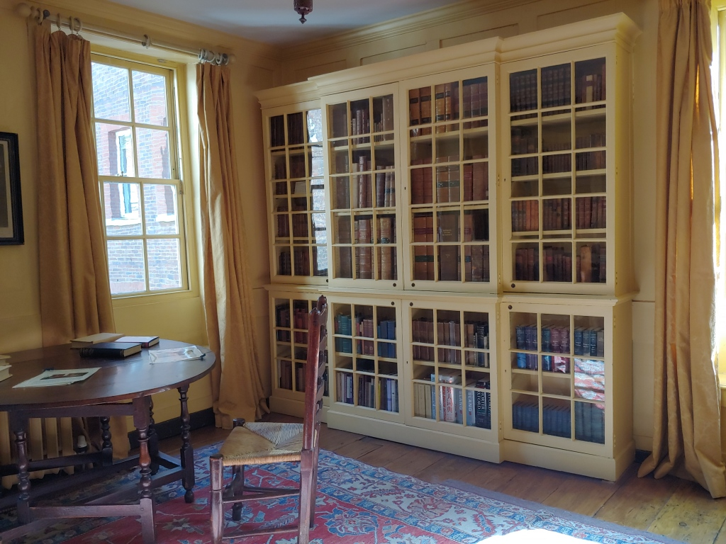 The room set up as a library, with a window in the corner, glass-fronted cupboard bookcases, and a small round table with chairs, where copies of books sit for visitors to read.