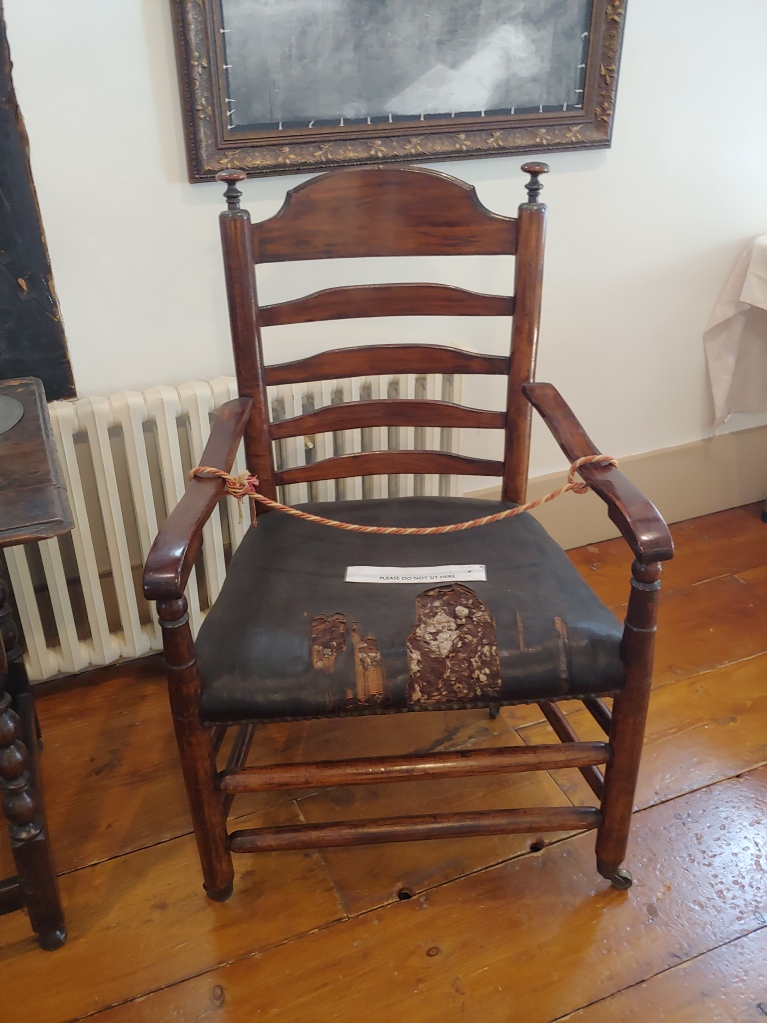 An old wooden chair with a worn leather seat.