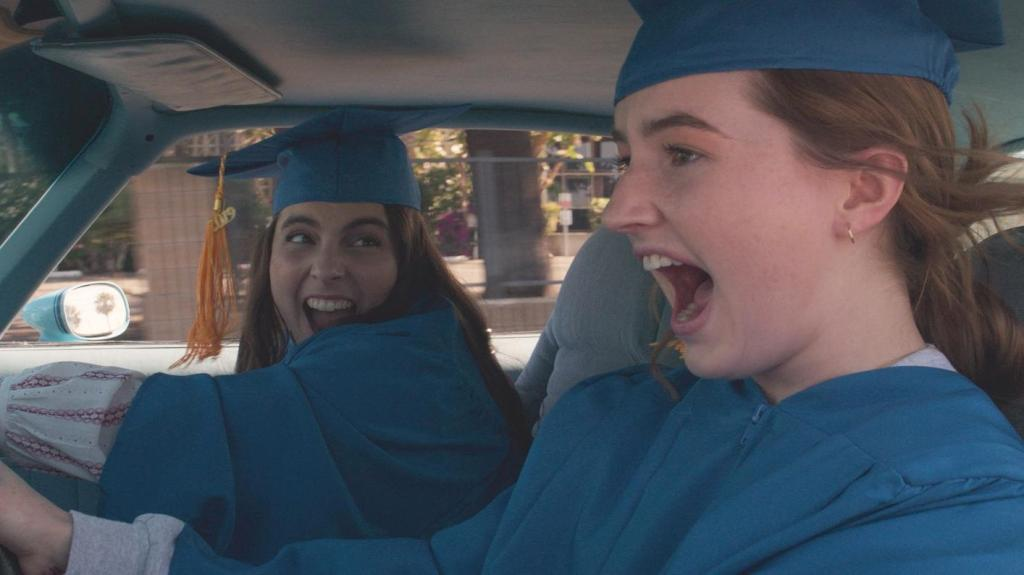 A still from the film 'Booksmart' showing a close up of two girls in blue academic graduation robes and mortarboards driving a car, both with mouths open in exclaimation.