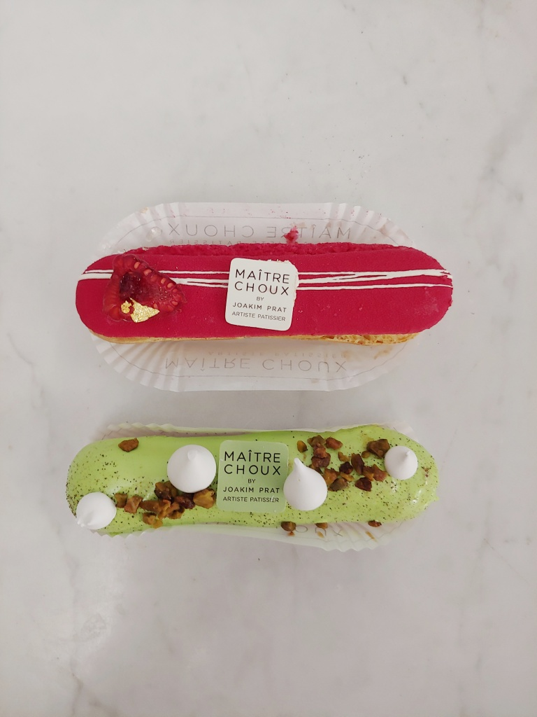 Photograph of a raspberry eclair and a pistachio eclair.  The raspberry one has a matte pink icing and is topped with half a raspberry with gold leaf on it.  The pistachio one has green icing and droplets of meringue and pistachio crumbs for decoration.