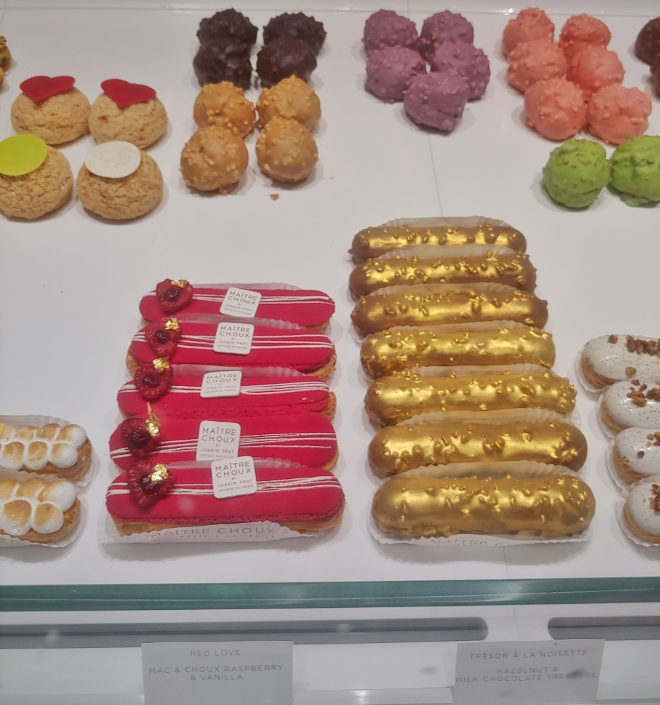 Photograph of the Maître Choux shop window with various colour choux buns and pastries.