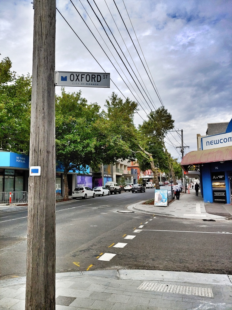 A view of a  tree-lined Melbourne street with a telegraph pole on the left, holding a sign reading 'Oxford St'.