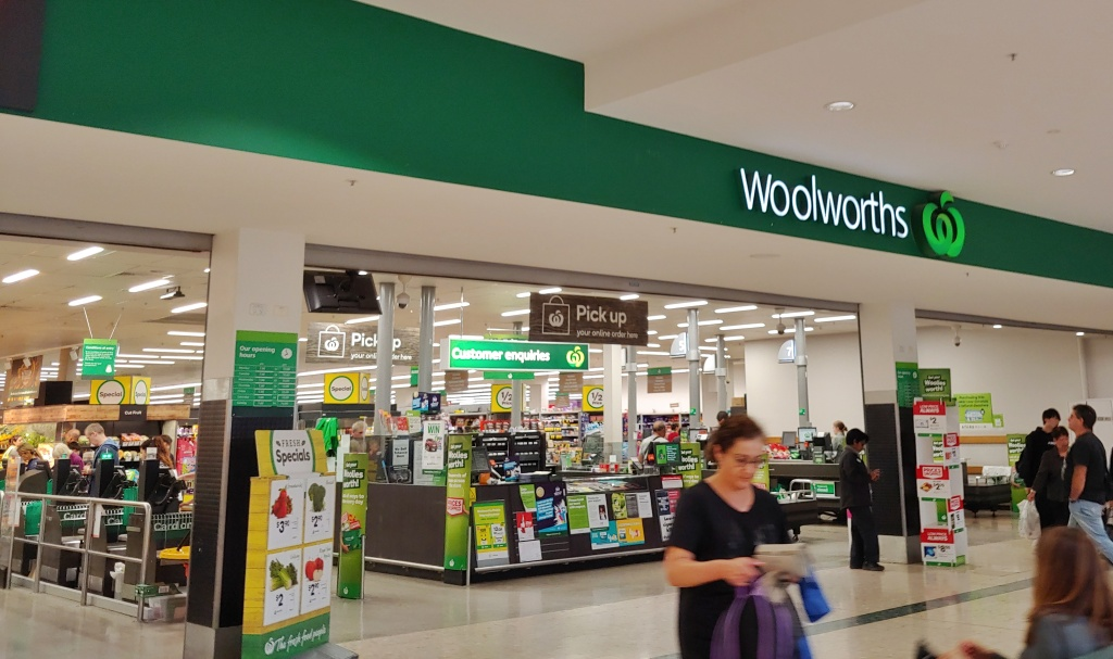 Image of the entrance to a Woolworths supermarket, with checkouts in the foreground, and shelves of fresh produce in the background.