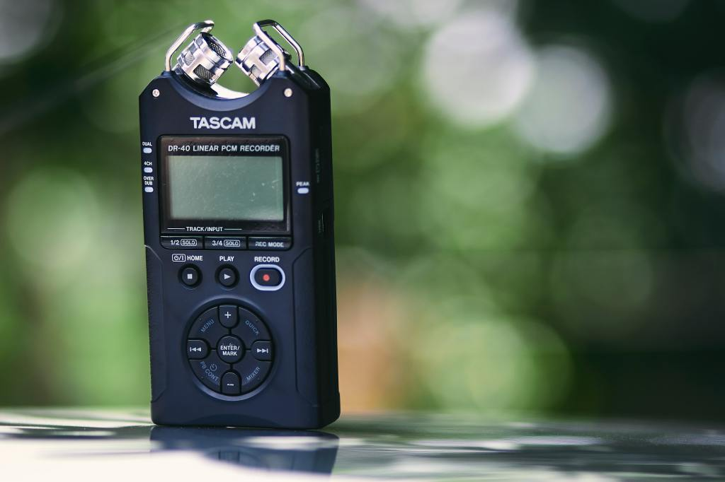 Close up image of a Tascam sound recording device with a green, leafy background