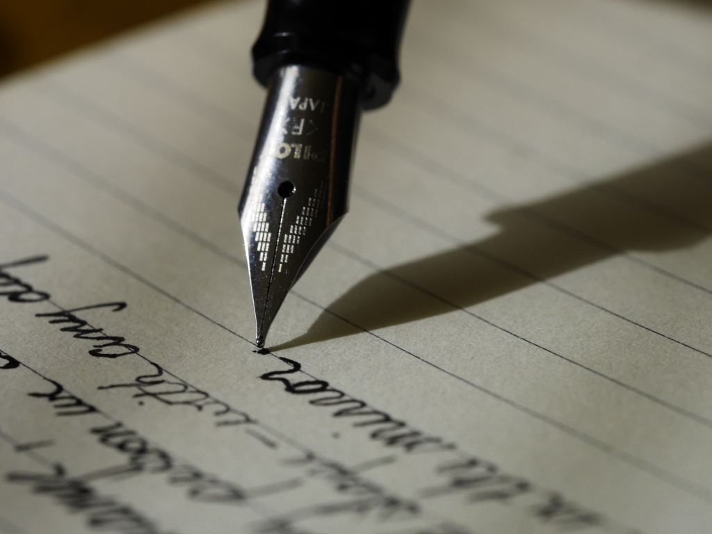 Image of a fountain pen writing in cursive on lined paper.