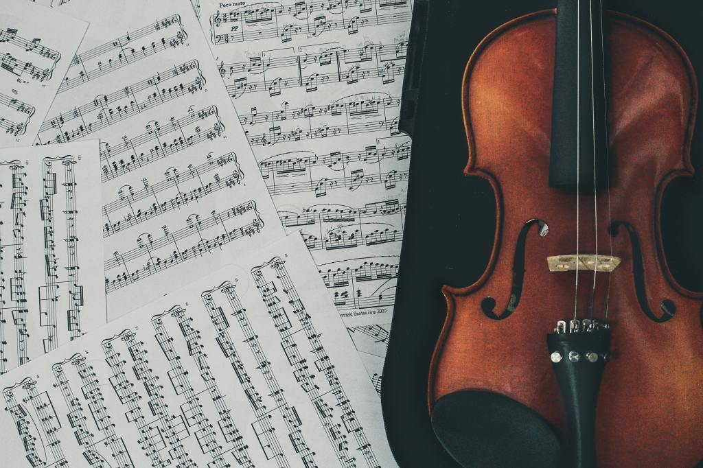 Classical music sheets overlap on the left with a violin placed in a black case on the right