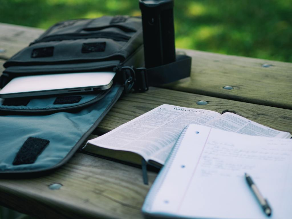 Notepad and open book on a wooden outdoor table next to a backpack with a laptop sticking out of it.