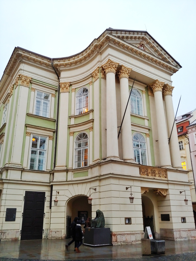 The Estates Theatre, Prage, with Neoclassical architecture, green walls, and cream columns with gold capitals.