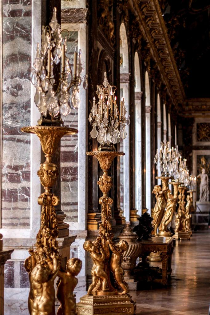 Image of the side of the Hall of Mirrors at Versaille, focusing on the large gilded candelbra.