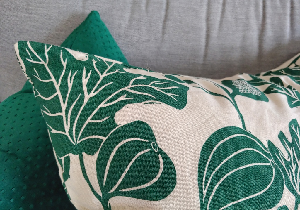 Close up of two cushions, one a green dimpled velvet texture and the other a thicker weave with a fig leaf print