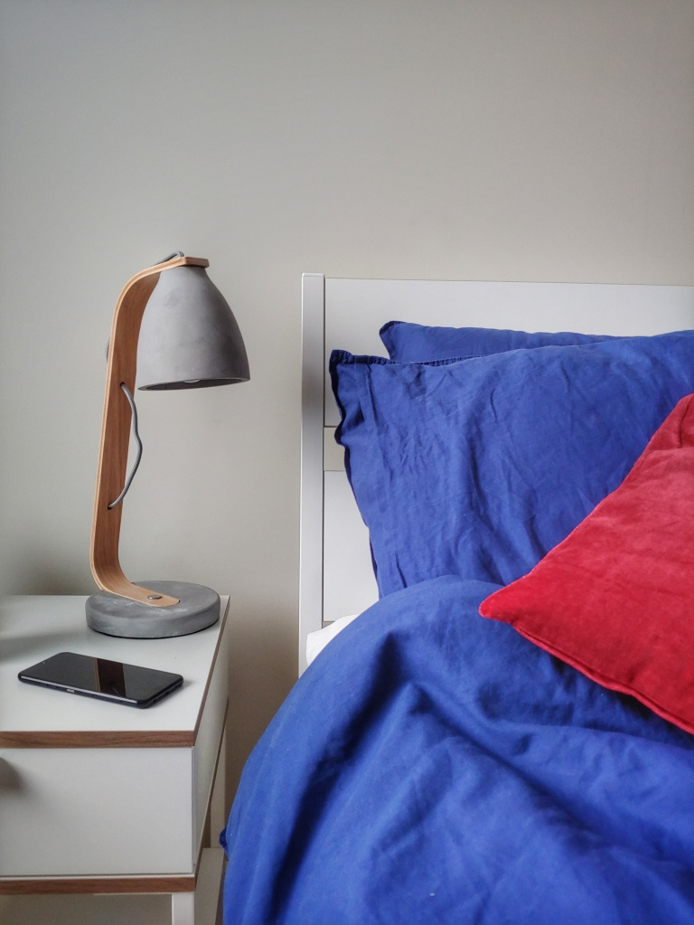 Close up of a bed with blue bedding and reddish pink cushion and a bedside table with a concrete lamp