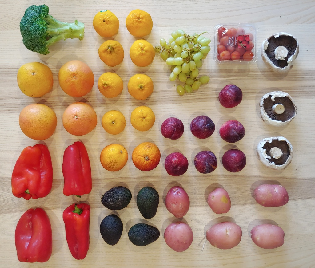 Fruit and vegetables arranged on a grid on a wooden table.
