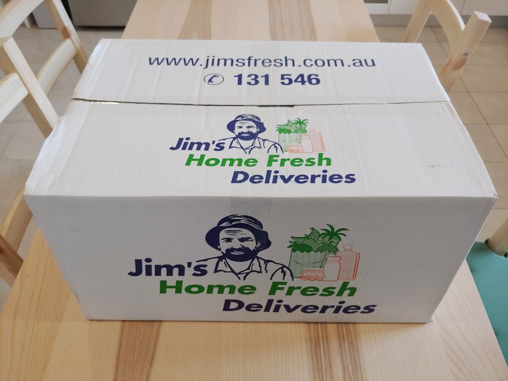 Unopened Jim's Home Fresh delivery box sitting on a wooden table.
