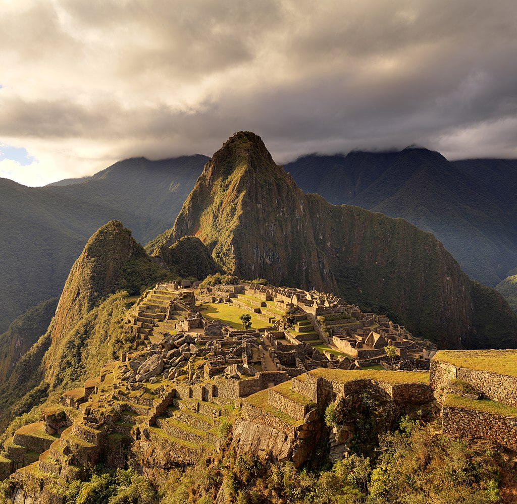 Image of Machu Picchu from further up the mountain, showing the intricate walls and the mountains in the background.