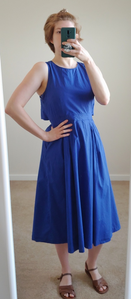 Full length photo of rich blue sleeveless A-line dress.