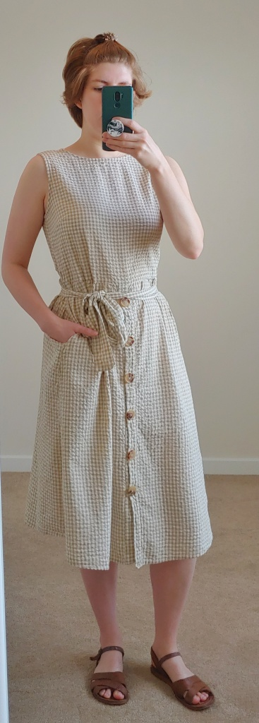 Full length photo of neutral colour gingham dress, with a fabric belt tied at the waist and buttons down the front of the skirt.