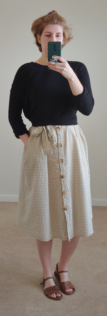 Full length photo of gingham dress with black jumper tied over it.