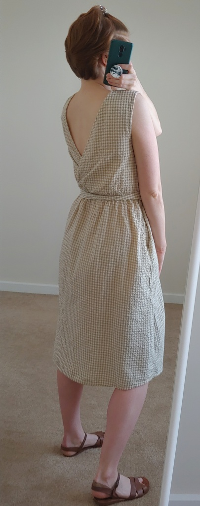 View of gingham dress from the back showing triangle wrap opening.