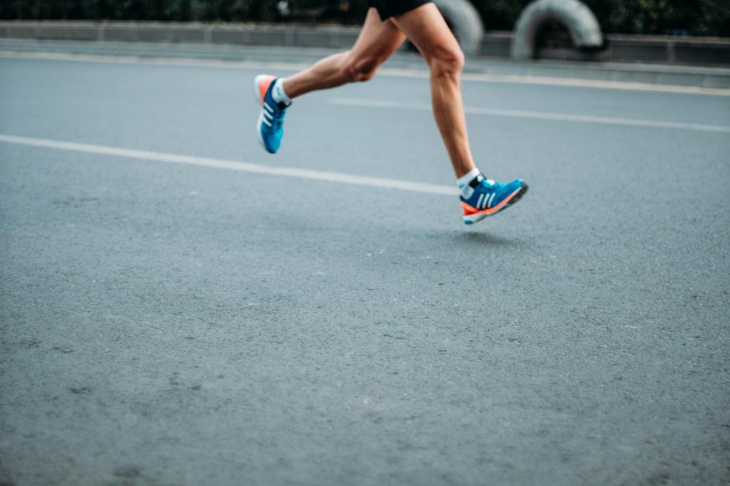 Runner's legs with blue shoes, in motion over tarmac