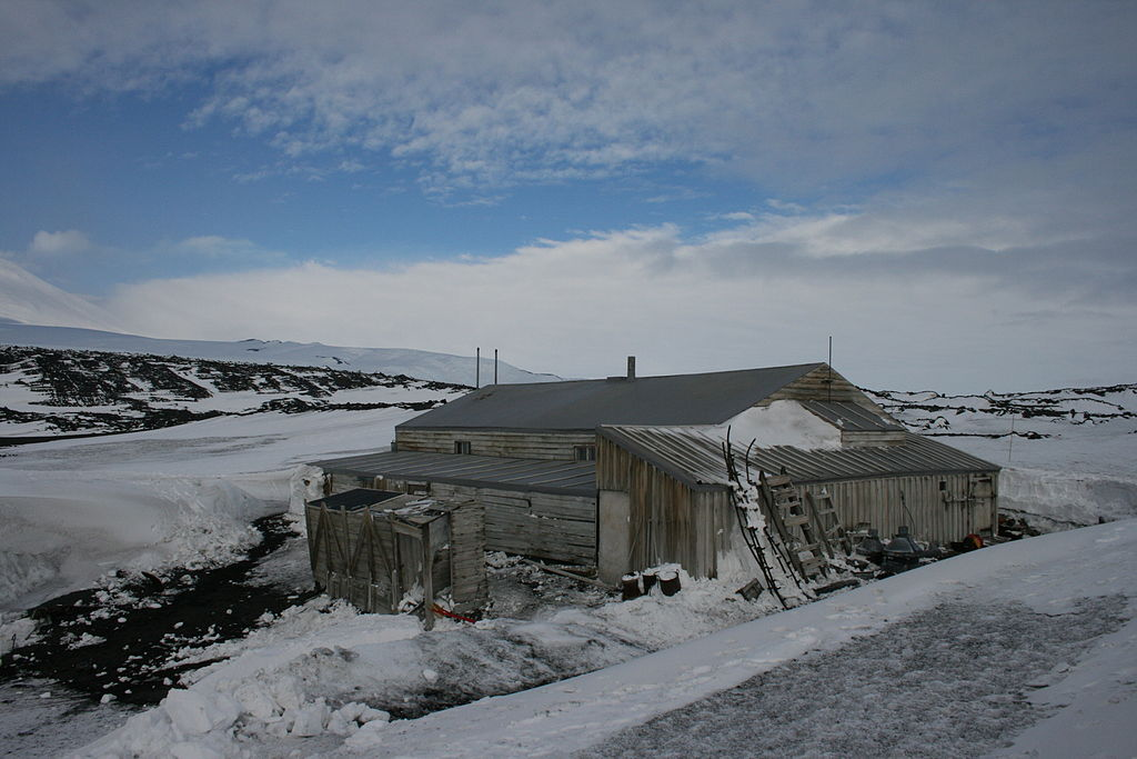 Image of Scott's Hut from the outside, with snowy hills in the distance, and a blue sky above.