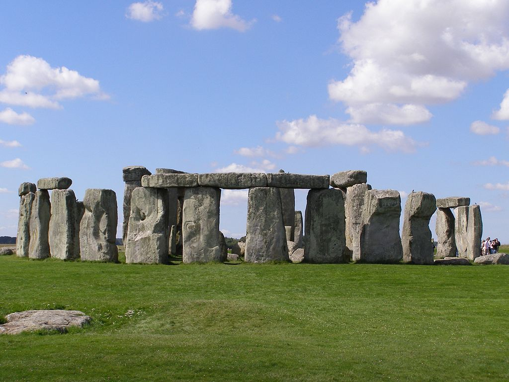Image of Stonehenge showing the stones on green grass with a blue sky above.