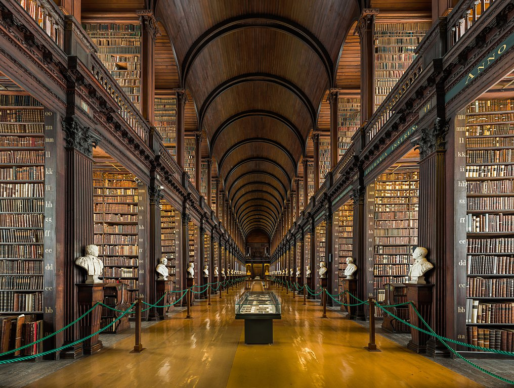 Image of the Long Room at Trinity College Dublin's Old Library, showing a barrel-vaulted ceiling and tall bookshelves on either side stretching into the distance.