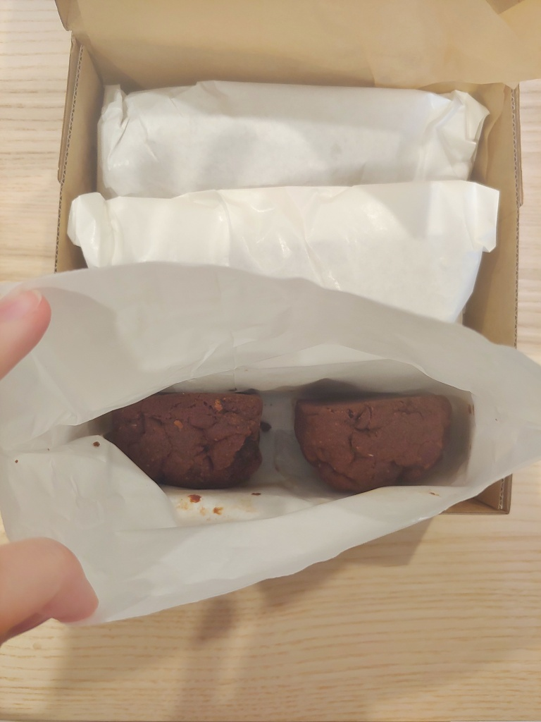 Open paper bag containing two The C Word choc chip cookies in a cardboard delivery box with other paper bags visible