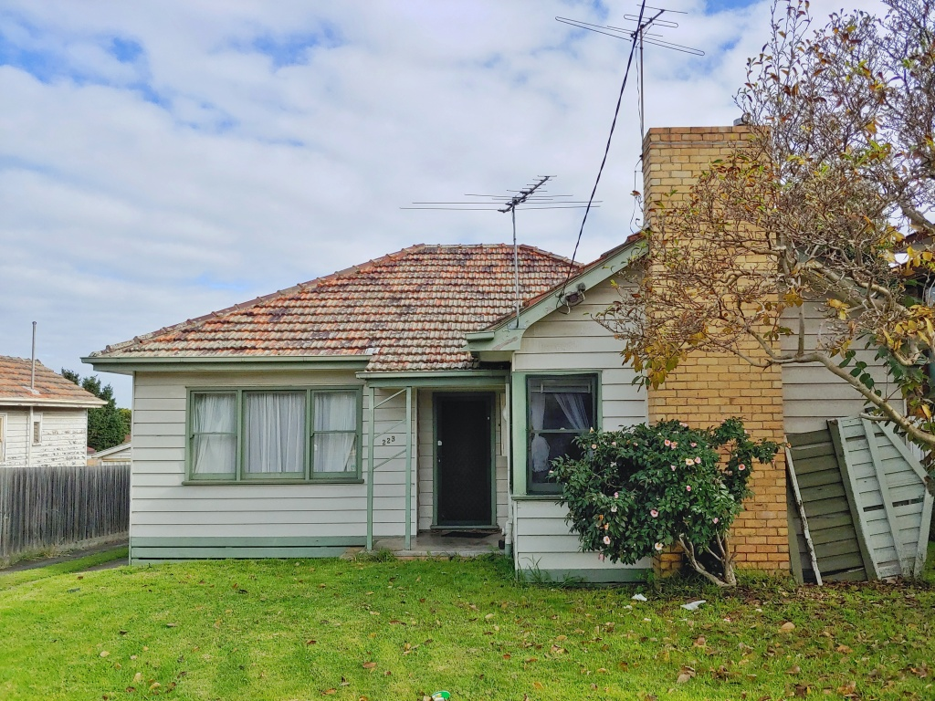 White paneled Australian bungalow with green accents, and a large brick chimney stack.