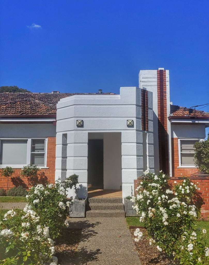 Red brick bungalow with white art deco style porch.