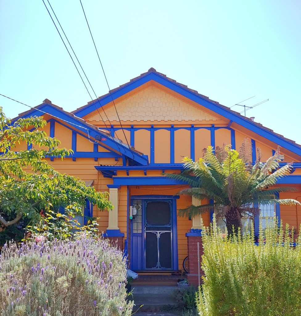 Bright yellow house with blue accents, a columned porch, and lavender and palm trees in the front garden.
