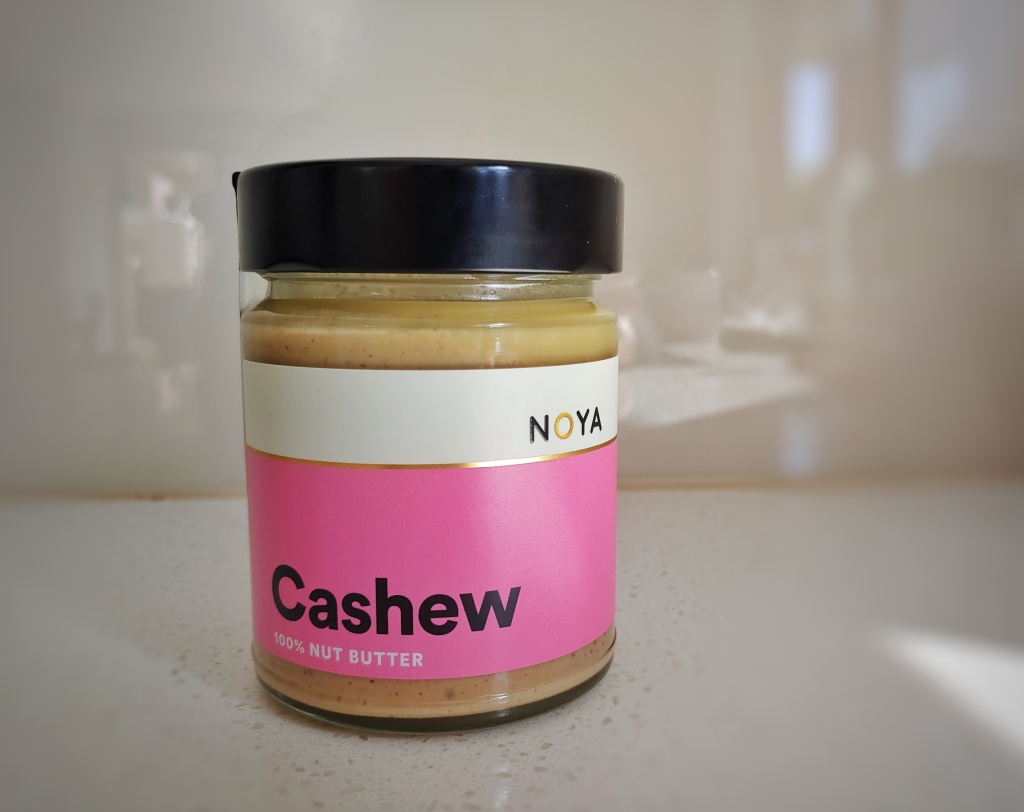 Jar of Noya cashew butter with a bright pink label and a black lid.
