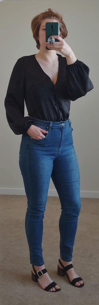 Full length photo wearing jeans, black block sandals and a black long-sleeved one-piece from Missguided.
