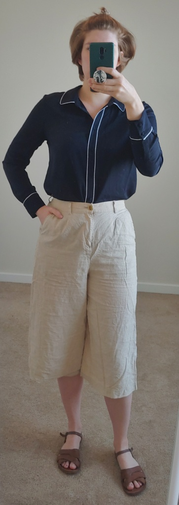 Full length photo wearing cream culottes, a navy and white piped shirt, and brown sandals.